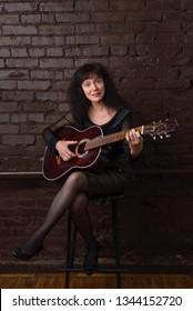 Beautiful adult woman playing guitar in the Studio.