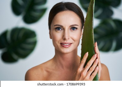 Beautiful adult woman posing against leaf background