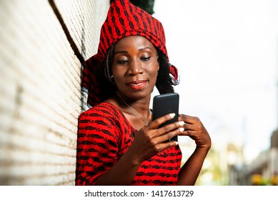 beautiful adult woman in red loincloth standing near a wall looking at her mobile phone while smiling.