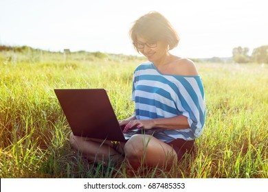 Beautiful  adult woman  sitting on the grass  and working on the computer. Using laptop outdoors, chatting with friends,