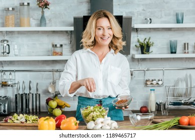 beautiful adult woman spilling spice onto lettuce in bowl at kitchen and looking at camera