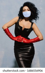Beautiful adult woman wearing in protection mask black spandex dress and long red leather gloves - image