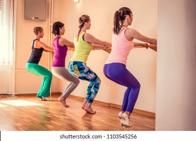 Beautiful adult women doing exercises on stretching ballet bar in Pilates class. Group of females doing yoga, pilates and fitness exercise indoors in studio.