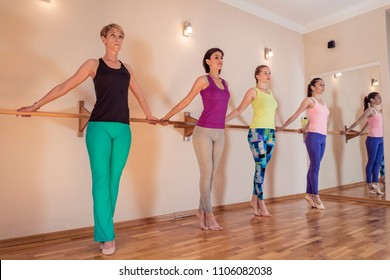 Beautiful adult women doing exercises on stretching ballet barre in Pilates class. Group of females doing yoga, pilates and fitness exercise indoors in studio.