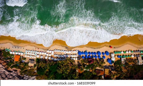 Beautiful aerial bird's eye view of the beach Praia do Madero located in Pipa in the state of Rio Grande do Norte, Brazil. The beach has many umbrellas, surf boards, Kayaks, and people enjoying it.
