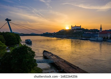 Beautiful aerial drone photo of Bratislava castle with Danube river, St. Martin's Cathedral and UFO tower and observation deck at sunset. Warm and colorful top view of old town cityscape from above. - Shutterstock ID 1682264206