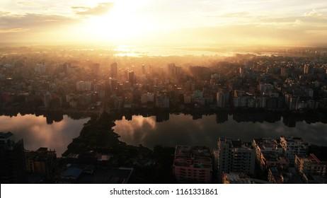 Beautiful aerial drone shot of sunrise over Dhaka skyline mist between buildings.