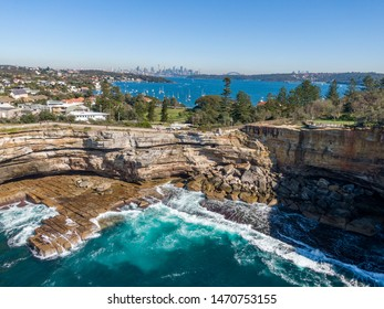 Beautiful aerial drone view of the Gap, an ocean cliff on the South Head peninsula in the suburb of Watson's Bay in eastern Sydney. The central business district of Sydney, Australia in background.