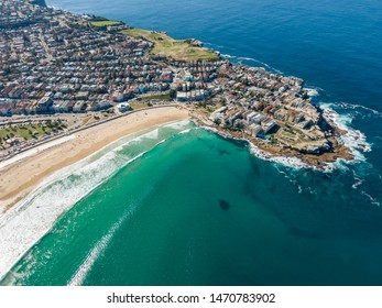 Beautiful aerial high angle drone view of the suburbs of Bondi Beach and North Bondi, one of the most famous beaches in Sydney, New South Wales, Australia. Large shoal of fish visible in the ocean.