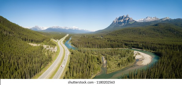 Beautiful aerial panoramic landscape view of a highway in Canadian Rockies during a vibrant sunny day. Taken in Banff, Alberta, Canada.