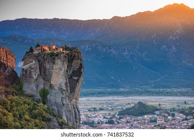 Beautiful aerial panoramic photo of the monasteries and rock formations of Meteora above Kalampaka city at sunset. Thessaly, Greece, Europe.