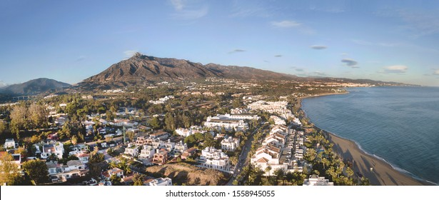 Beautiful aerial Panoramic View of Marbella, Nueva Andalucia and Puerto Banus area. Beautiful colours at sunset. La Concha mountain in background.
