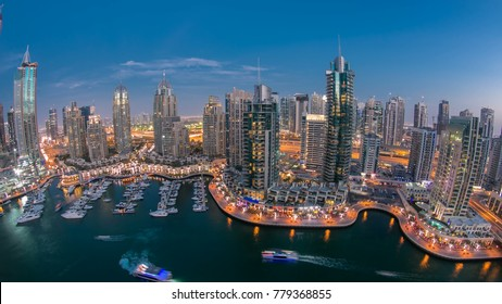 Beautiful aerial  top view day to night timelapse of Dubai Marina promenade and canal with floating yachts and boats after sunset in Dubai, UAE. Modern towers and traffic on the road. Fisheye lens