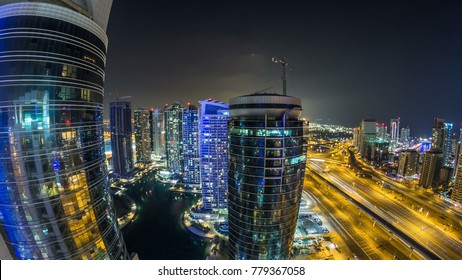 Beautiful aerial top view at night timelapse of Dubai Marina  and JLT skyscrapers in Dubai, UAE. Illuminated modern towers with blinking lights, lake and traffic on the road with metro line and tra