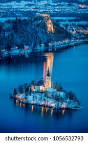 Beautiful aerial twilight view of Lake Bled with famous Bled Island and historic Bled Castle in the background during scenic blue hour at dawn in winter, Slovenia