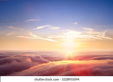 Beautiful aerial view above clouds with sunset. Airplane view