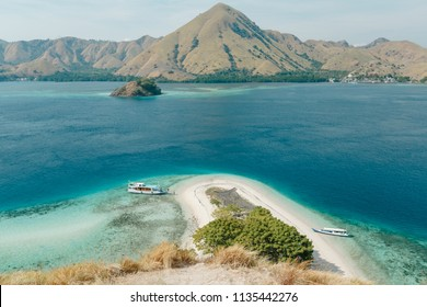 Beautiful aerial view of beaches and tourist boat sailing in Flores Island, Indonesia. Looking Out from the Top of Kelor Island (Pulau Kelor), near Komodo National Park