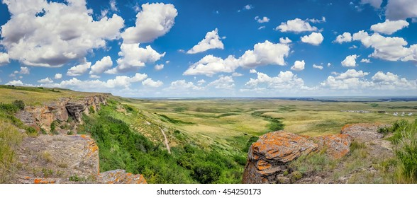 Beautiful aerial view of Canadian Prairie at Head-Smashed-In Buffalo Jump world heritage site in Southern Alberta on a sunny day with blue sky and clouds in summer, Canada