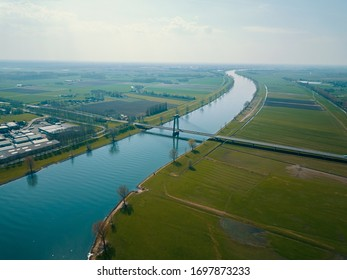 Beautiful aerial view of the canal, bridge and big ram fields in the Netherlands