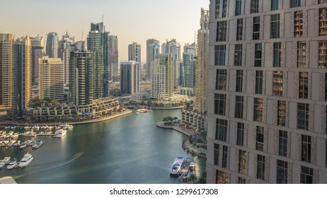 Beautiful aerial view of Dubai Marina promenade and canal with floating yachts and boats before sunset in Dubai, UAE. Modern towers and skyscrapers with windows at evening