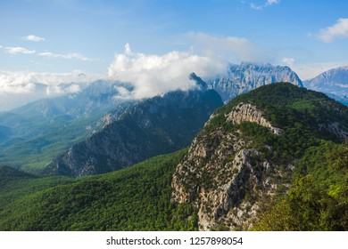 Beautiful aerial view at green woody hills of mountains in Turkey. Hills with thick woods growing and blue sky with fluffy white clouds at peaks of hills. Horizontal color photography.