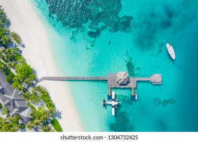 Beautiful aerial view of Maldives jetty seaplane top view with wooden boat Dhoni and tropical beach, palm trees and white sand. Luxury travel and vacation concept. Amazing aerial landscape