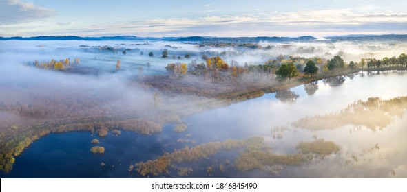 Beautiful aerial view of morning fog and sunrise in autumn forest.