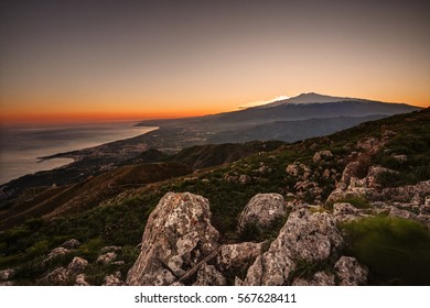 Beautiful aerial view of mount Etna at sunset and of the coastline between Taormina and Giardini Naxos in Sicily, Italy.