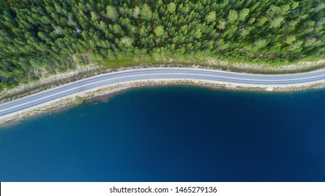 Beautiful aerial view of road between green summer forest and blue lake in Lapland.