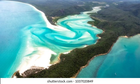 A beautiful aerial view of turquoise waters, white sandy beaches and green forests in the paradise of the Whitsunday's islands, Australia. Concept for summer, holidays and travelling