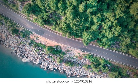 The beautiful aerial view of the Vung Ro Bay coast road with emerald green ocean, white stones on the roadside, dark green trees - Film style