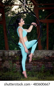 Beautiful aerialist girl doing some tricks on aerial ring with palm torches