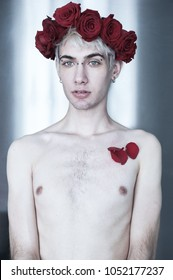Beautiful aesthetic guy with red flowers on his head and red petals