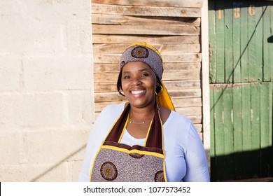 Beautiful afican lady standing infront of her township house.