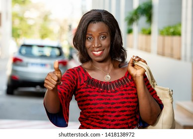 beautiful african adult business woman returning from work in a sunny day, shows her thumb accompanied by a beautiful smile in the street outdoors