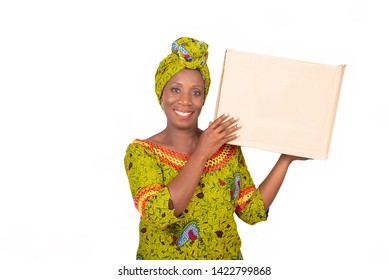 beautiful african adult woman dressed in loincloth and green headscarf, smiling holding in both hands a cardboard box