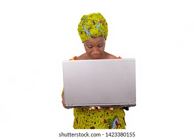 beautiful african adult woman dressed in loincloth and green scarf is standing while handling a portable computer in hand with a beautiful smile