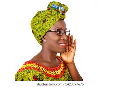 beautiful african adult woman dressed in loincloth and green head scarf wearing beautiful eyeglasses is all smiling and makes a gesture of talking with the hands aside