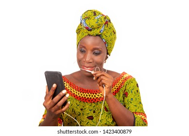 beautiful African adult woman dressed in loincloth and green scarf is communicating with his headphones in his mobile phone while smiling