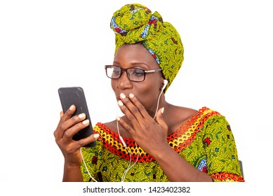 beautiful african adult woman dressed in loincloth and green scarf with glasses, takes pleasure listening to music with headphones, in her cellphone.