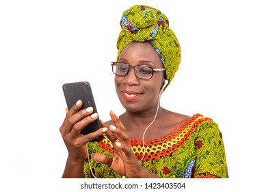 beautiful african adult woman dressed in loincloth and green scarf with glasses, takes pleasure communicating with headphones, in his mobile while smiling