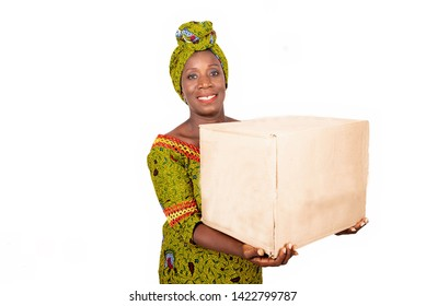 beautiful african adult woman wearing a loincloth and green scarf, smiling holding a cardboard box in the hand