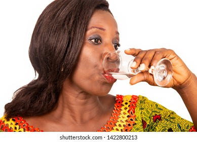 beautiful African adult woman wearing a green loincloth with long black hair, is drinking mineral water in a glass on a white background.