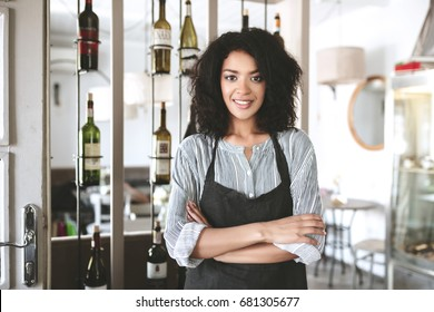 Beautiful African American barista girl in apron standing with arms folded in restaurant. Young girl with dark curly hair standing in apron at cafe. Portrait of smiling waitress wearing uniform