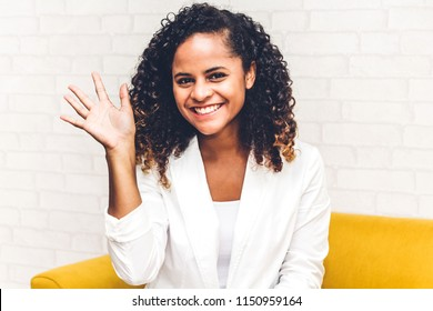 Beautiful african american black woman smiling at camera waving and saying hello to you