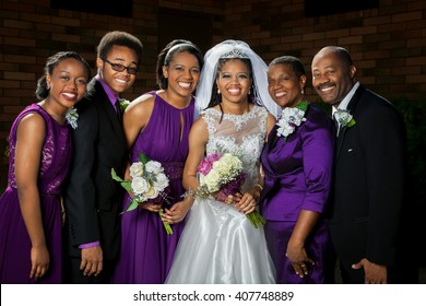 A beautiful African American bride poses for a picture with her family before her wedding.