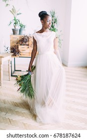Beautiful african american bride with tropical bouquet in studio