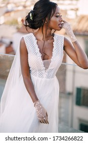 Beautiful African American bride in a white wedding dress, touches her face in vintage gloves. Fine-Art Wedding in Florence, Italy.