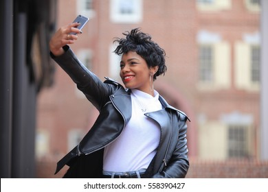 Beautiful African American brunette woman feeling cold and smiling with phone taking her own photo selfie, while standing in autumn spring forest outdoors wearing black leather jacket, afro-american
