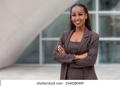 Beautiful african american business woman portrait, arms folded, confident happy CEO